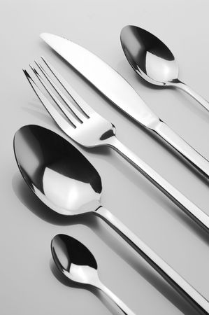 Set of stainless spoons, knife and fork on light background. B&W.