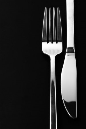 Stainless knife and fork on black background with copy space. Stock Photo