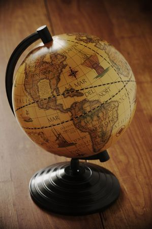 Vintage globe in back light on wooden surface.