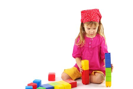 Nice little girl playing with colorful bricks on white background. photo