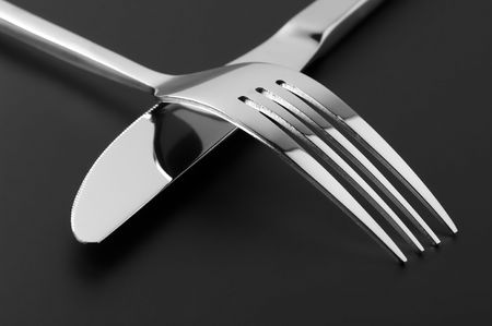Close-up of stainless fork and knife on dark background.