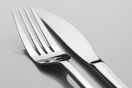 Acero inoxidable cuchillo y tenedor sobre fondo claro. B&W.
