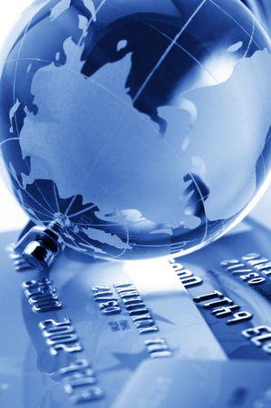 banking: Close-up of glass globe on credit cards. Toned monochrome image. Shallow DOF. Stock Photo