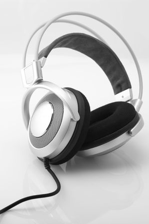 Silver headphones with cable on light background.