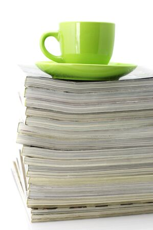 Stack of magazines and green cup of coffee isolated on white background. Stock Photo - 6484781