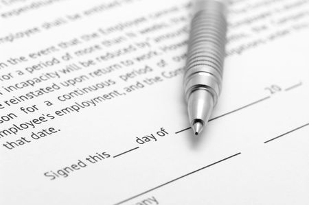 Close-up of silver pen on employment agreement. Selective focus on top of pen.