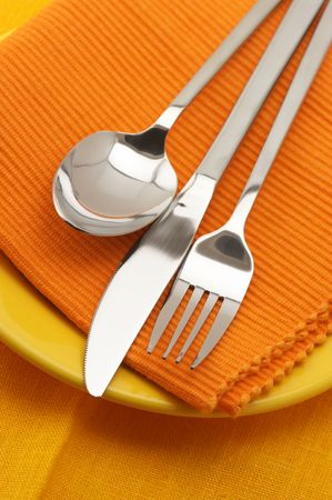 Stainless spoon, fork and knife on yellow plate with orange linen napkin. Stock Photo