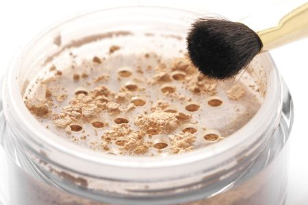 Close-up of cosmetic loose powder in jar with brush on white background. photo
