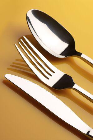 cuchillo y tenedor: Cuchillo de acero inoxidable, tenedor y cuchara sobre fondo amarillo.