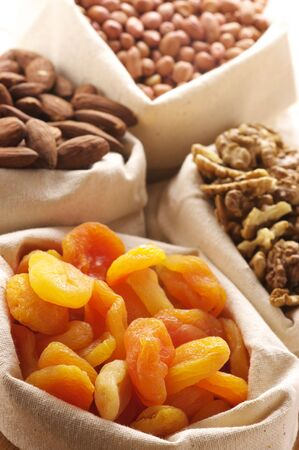 Heap of nuts and dried apricots in canvas bags. Focus on apricots. photo