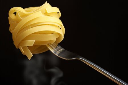 ribbon pasta: Raw pasta (tagliatelle) on fork over rising steam against black background. Stock Photo