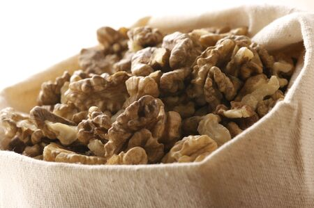 Heap of raw walnuts in canvas bag. photo