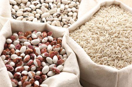 legumbres secas: Varios haricots y arroz en bolsas de lona.