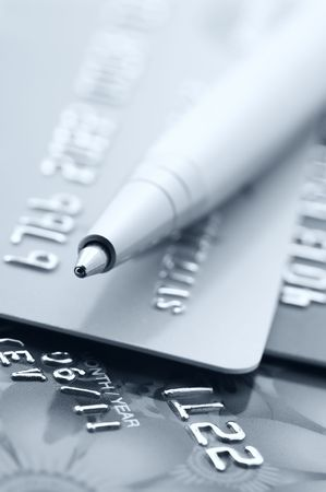 Close-up of silver pen on credit cards. Toned monochrome image. Selective focus on top of pen. Stock Photo - 6587867