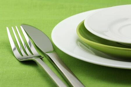 White and green plates, stainless fork and knife on green linen tablecloth. Stock Photo