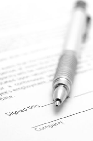 Close-up of silver pen on employment agreement. Selective focus on top of pen. photo