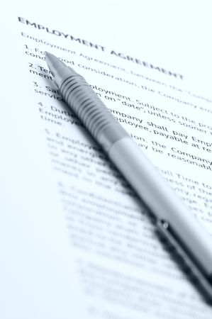 Close-up of silver pen on employment agreement. Selective focus on top of pen. Toned monochrome image. photo