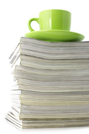 Stack of magazines and green cup of coffee isolated on white background. photo