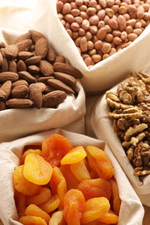 Heap of nuts and dried apricots in canvas bags. Focus on apricots. Stock Photo - 6718975
