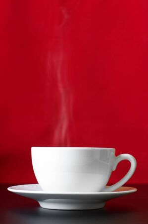 White cup of coffee with steam and saucer on redblack background. photo