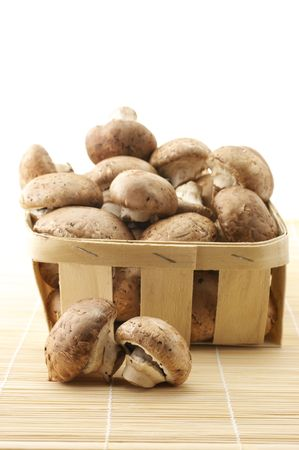 bast basket: Mushrooms (Agaricus bisporus) in retail bast basket on mat. Stock Photo