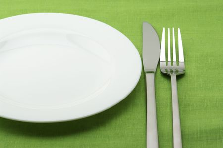 White plate, stainless fork and knife on green linen tablecloth. photo