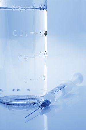 physiologic: Glass bottle of sterile physiologic solution and syringe close-up. Toned monochrome image.
