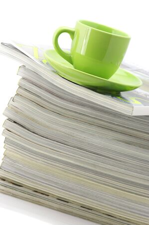 Stack of magazines and green cup of coffee on white background. photo