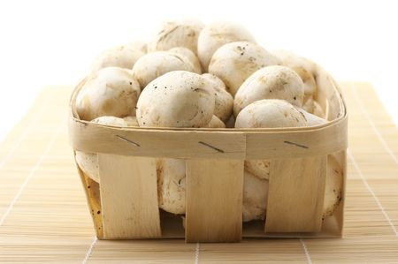 bast basket: Porcelain agarics in retail bast basket on mat. Stock Photo