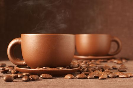 Two brown ceramic cups of coffee with steam and coffee beans on brown canvas.  photo