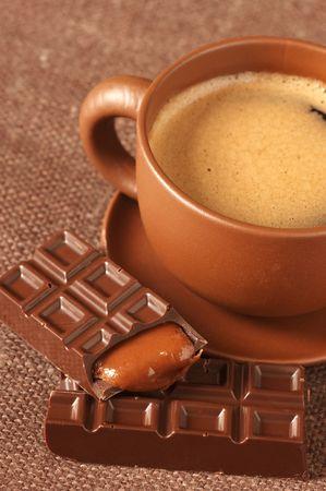 opvulmateriaal: Bruine keramische kopje koffie met froth en verbroken chocolade balk met karamel stuffing op bruine canvas. Stockfoto