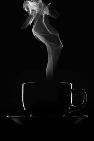 Black cup of coffee with steam on black background. photo