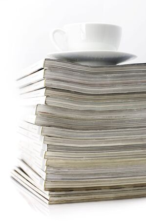 Stack of magazines and white cup of coffee on light background. photo