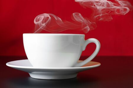 White cup of coffee with steam on redblack background. photo