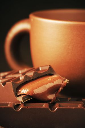 Brown ceramic cup of coffee and broken chocolate bar with caramel stuffing close-up. photo