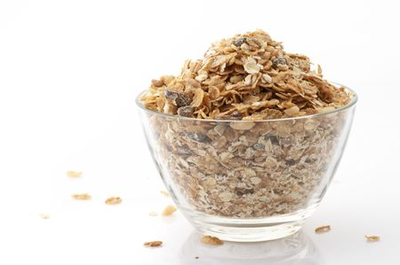 Glass bowl with muesli isolated on white background.