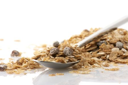 Heap of muesli and metallic spoon on white background. photo