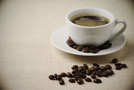 Black coffee in white cup and coffee beans on beige canvas. Retro-stylized image. Stock Photo