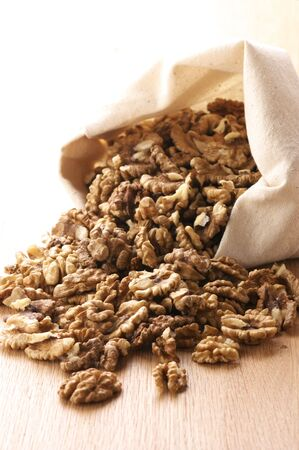 Heap of raw walnuts spill out canvas bag. photo