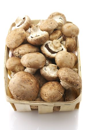 bast basket: Mushrooms (Agaricus bisporus) in retail bast basket isolated on white background.