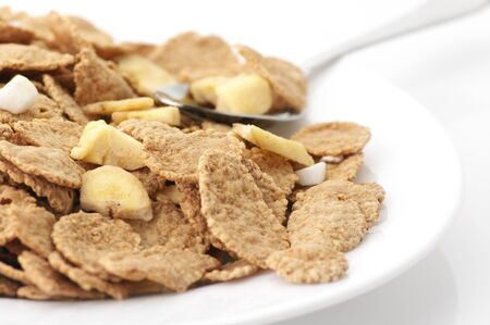 roughage: Heap of breakfast cereal in white plate with spoon on white background.