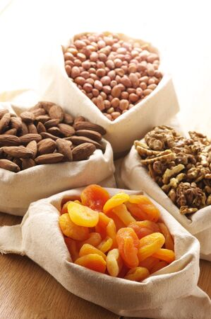 Heap of nuts and dried apricots in canvas bags. Focus on apricots. Stock Photo - 7055812