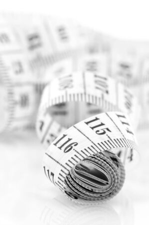 unwound: Unwound white tape measure with black scale on light background. Stock Photo