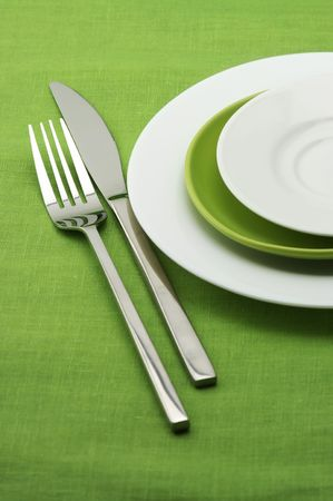 White and green plates, stainless fork and knife on green linen tablecloth. photo