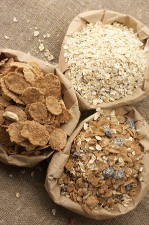 Various breakfast cereals in paper bags on brown canvas. photo