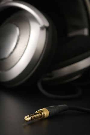 audio equipment: Close-up of gilded jack against silver headphones. Selective focus on top of jack.
