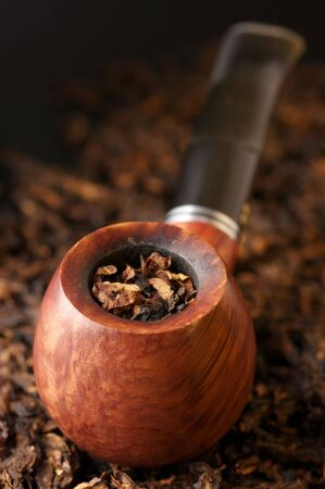Wooden pipe on heap of chopped dried tobacco leaves. photo