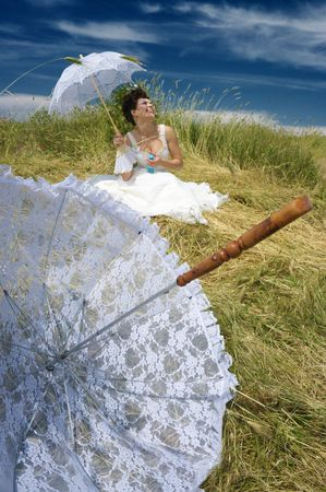 Lace umbrella and beautiful bride sitting in field. photo