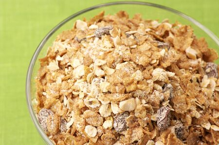 roughage: Close-up of glass bowl with muesli on green background. Stock Photo
