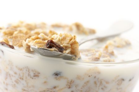 Close-up of muesli in spoon on glass bowl of muesli with milk. photo